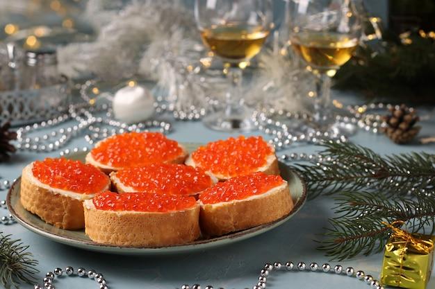 Panini con caviale rosso su crostini di pane bianco su un piatto su fondo azzurro