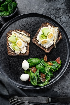 Panini con sarde, uovo, cetriolo e crema di formaggio, guarnire l'insalata con spinaci e pomodori secchi. sfondo nero. vista dall'alto.