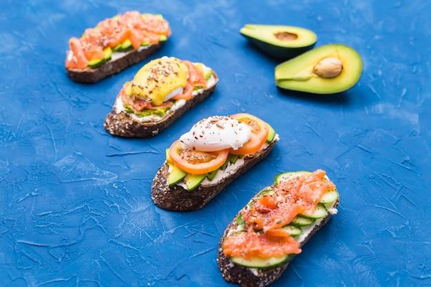 Panini con salmone affumicato, uova, salsa e avocado su sfondo blu. concetto di colazione e