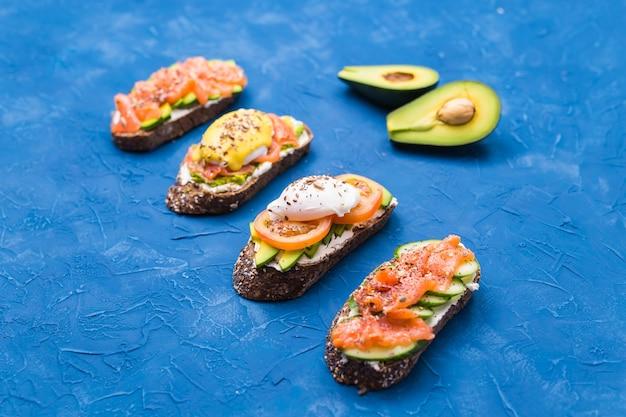 Panini con salmone affumicato, uova, salsa e avocado sulla superficie blu. concetto di colazione e