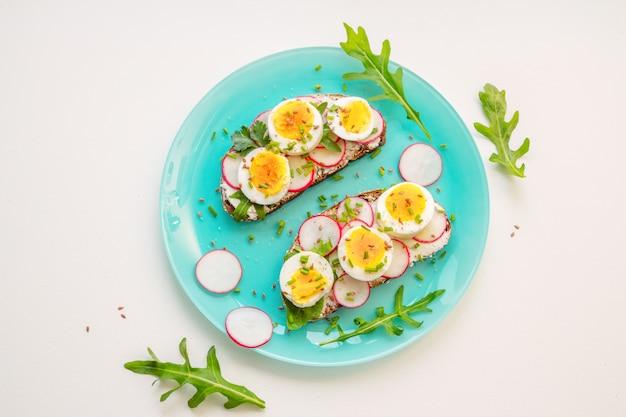 Panini con uovo sodo morbido, avocado, ravanello, rucola, cipolla verde e semi di lino sul piatto blu. snack salutare.