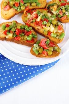 Panini con verdure e verdure sulla piastra sul primo piano del tavolo in legno