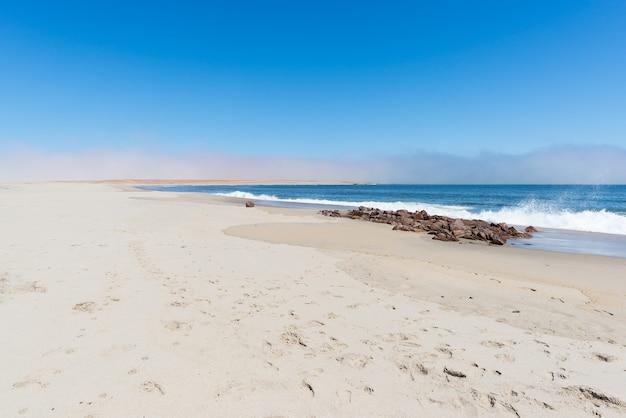 Spiaggia di sabbia e linea costiera sull'oceano atlantico a cape cross, namibia