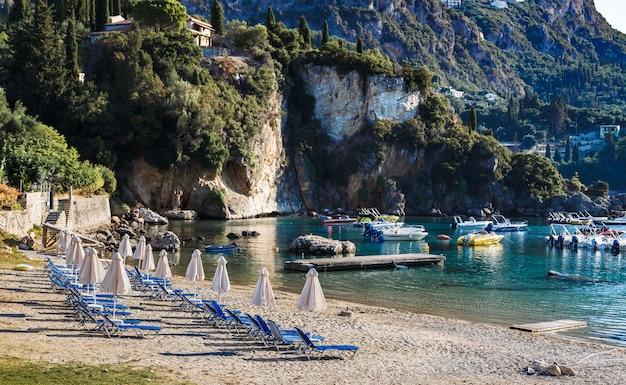 Spiaggia di sabbia a paleokastritsa corfu grecia al mattino lettini ombrelloni barche acqua cristallina
