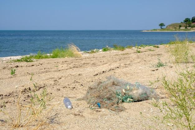 Spiaggia di sabbia vicino al mare in una giornata di sole estivo. sulla sabbia giace una rete da pesca aggrovigliata. il risultato dell'attività dei bracconieri. concetto di protezione della natura.