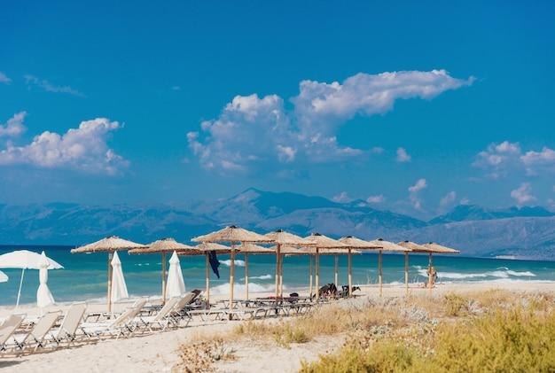 Spiaggia sabbiosa del mare con molti lettini e ombrelloni di paglia