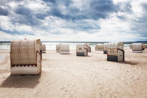Spiaggia di sabbia con sedie a sdraio. paesaggio di fine estate con cielo molto nuvoloso. sfondo di vacanza. costa del mar baltico, destinazione di viaggio