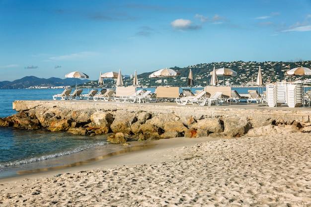Spiaggia di sabbia con lettini vuoti sul molo in una giornata di sole presso il resort. riviera francese. turismo e viaggi.