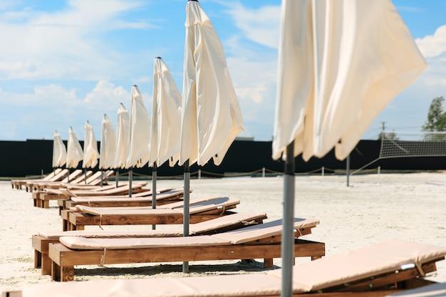 Spiaggia di sabbia con molti lettini e ombrelloni chiusi in fila. tempo soleggiato all'aperto. bellissimo posto per rilassarsi durante il periodo estivo.