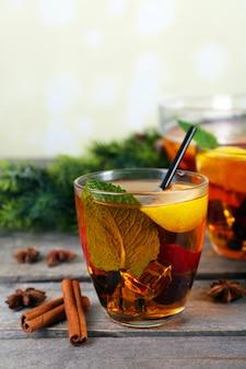Sangria in ciotola e bicchieri con decorazioni natalizie sul tavolo di legno vicino