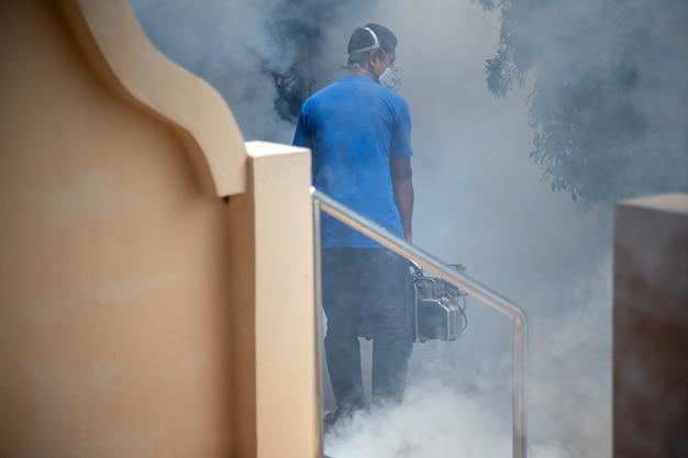 Sanificazione da virus. un uomo in un respiratore spruzza un antisettico.
