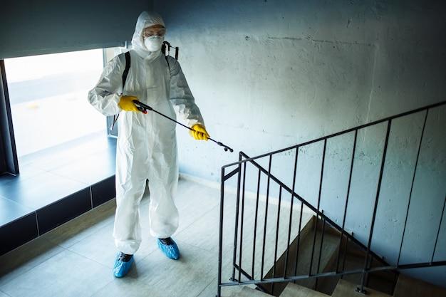Igienizzazione del lavoratore che pulisce le scale del centro commerciale con un antisettico per prevenire la diffusione del covid-19. un uomo in tuta per la disinfezione spruzza le scale.