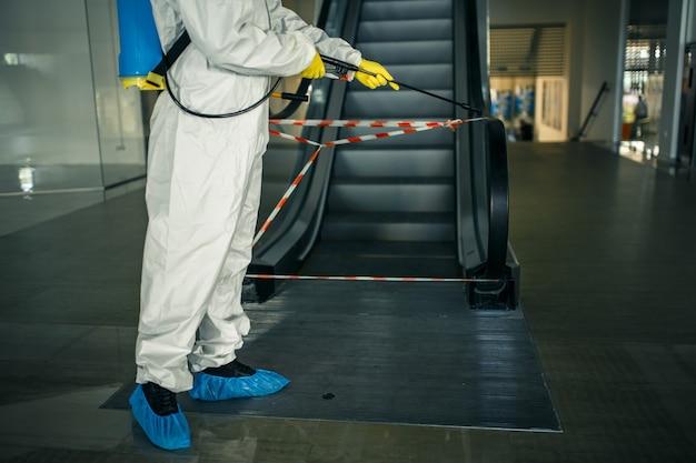 Il lavoratore disinfettante disinfetta la scala mobile con uno spray nel centro commerciale vuoto per evitare che il covid-19 si diffonda nei luoghi pubblici.
