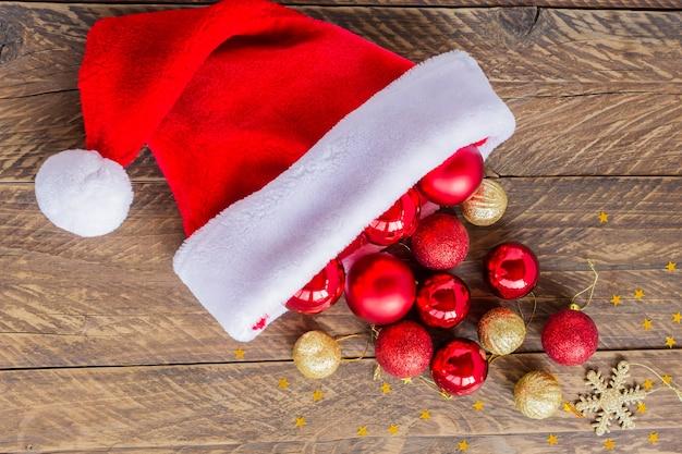 Berretto da babbo natale con palline rosse e dorate sparse per la decorazione dell'albero di natale. biglietto di auguri festivo