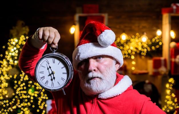Babbo natale festeggia il natale santa man tenere l'orologio di capodanno orologio di natale vacanze invernali tempo per