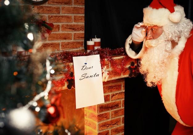 Babbo natale ha portato i regali per natale e per riposarsi accanto al caminetto. decorazioni per la casa