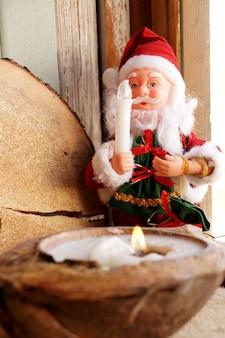 Babbo natale e una candela in un cocco decorativo