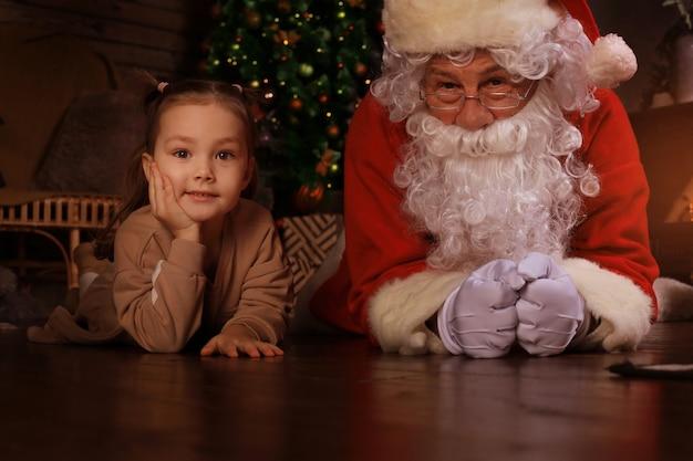 Babbo natale e bambino sdraiati sul pavimento a casa. regalo di natale. concetto di vacanza in famiglia.