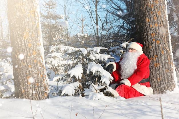 Babbo natale arriva con i regali dall'esterno. babbo natale in abito rosso con barba e occhiali sta camminando lungo la strada per natale. babbo natale porta i regali ai bambini.