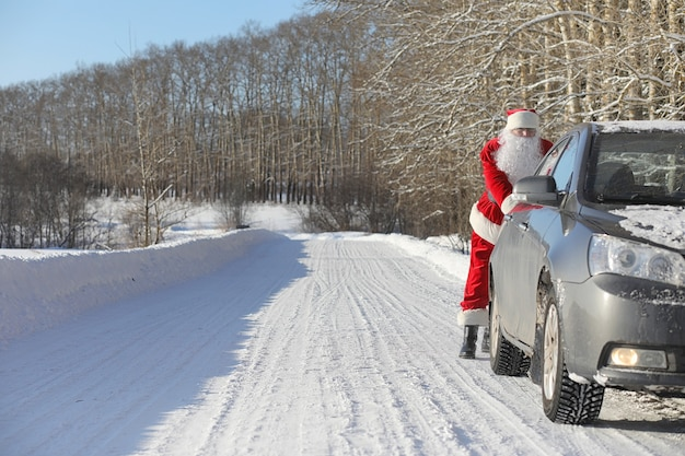 Babbo natale arriva con regali dall'esterno. babbo natale in abito rosso con barba e occhiali sta camminando lungo la strada per natale. babbo natale porta i regali ai bambini.