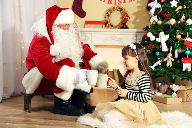 Babbo natale beve cioccolata calda con una bambina carina vicino all'albero di natale a casa
