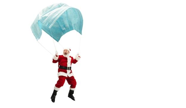 Babbo natale che vola su un'enorme maschera facciale come su un palloncino isolato su sfondo bianco