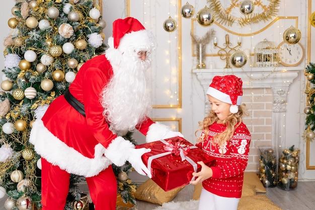 Babbo natale fa un regalo a una bambina all'albero di natale, il concetto di nuovo anno e natale
