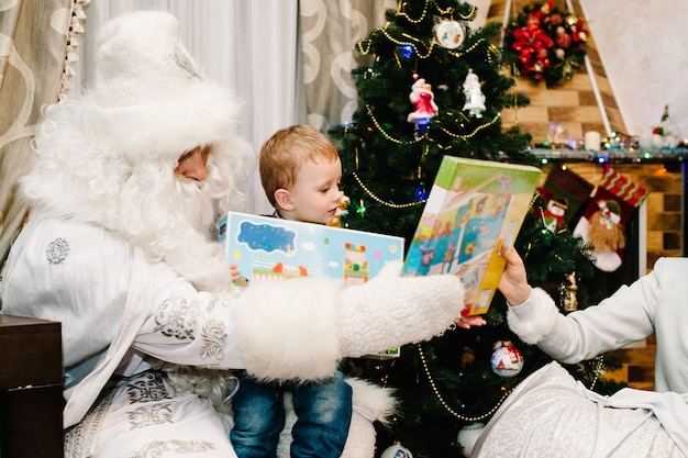 Babbo natale che fa un regalo a un ragazzino carino in braccio vicino al camino e all'albero di natale a casa. snow maiden ha portato regali ai bambini. concetto di nuovo anno. buon natale. vacanze.