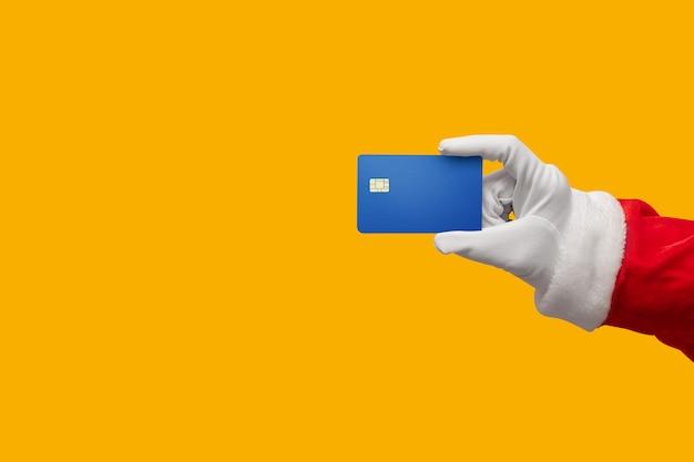 Mano di santa claus che giudica la carta di credito blu su giallo o sull'arancia isolata.
