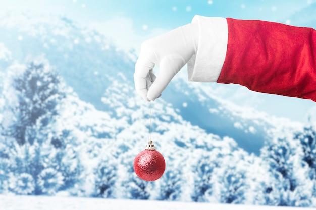 Mano di babbo natale che tiene palla di natale con nevicate. buon natale