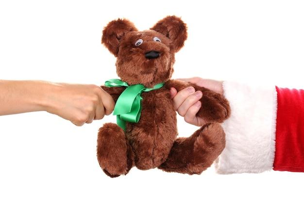 Babbo natale che tiene in mano un orso giocattolo isolato su bianco