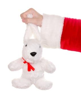 Babbo natale mano azienda coniglio giocattolo isolato su white