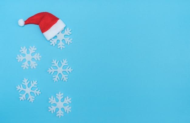 Cappello di babbo natale e fiocchi di neve su sfondo blu pastello. concetto invernale minimo. biglietto di auguri di natale