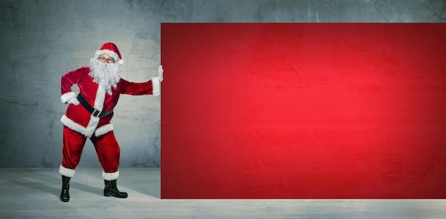 Santa claus che tiene sull'insegna in bianco della pubblicità con copyspace. tema natalizio, saldi