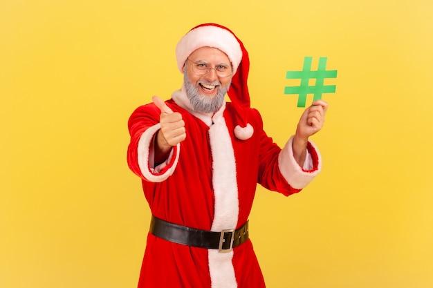 Babbo natale che tiene in mano l'hashtag verde e mostra il pollice in su, sito web consigliato