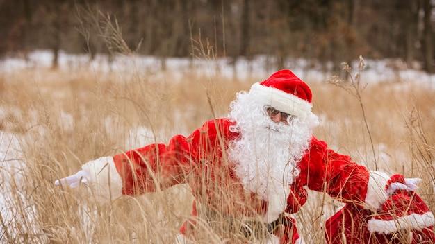 Babbo natale che tiene in un sacchetto rosso i regali per i bambini per natale va su un campo invernale