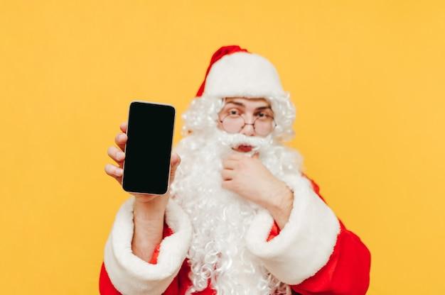 Babbo natale sta attirando l'attenzione mostrando uno smartphone