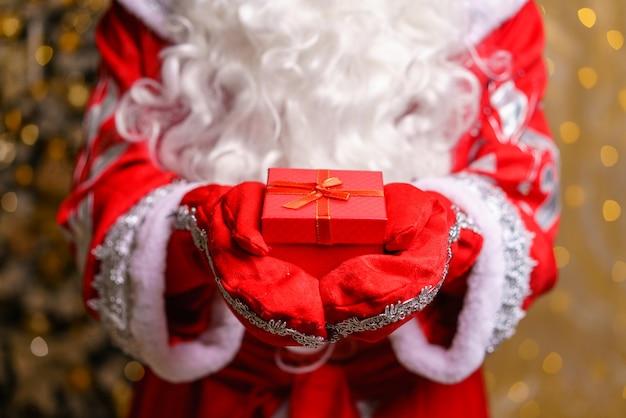 Babbo natale tiene in mano una piccola scatola rossa regalo di natale in entrambe le mani in formato orizzontale che mostra solo il...
