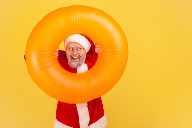 Babbo natale che guarda attraverso l'anello di gomma arancione, copia spazio per la pubblicità.