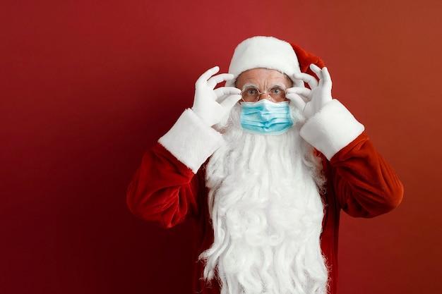 Babbo natale in una maschera medica su uno sfondo rosso.