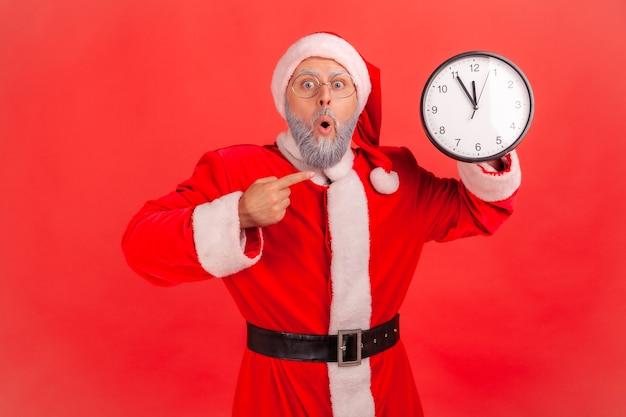 Babbo natale che indica l'orologio da parete in attesa di appuntamento, tenendo la bocca aperta.