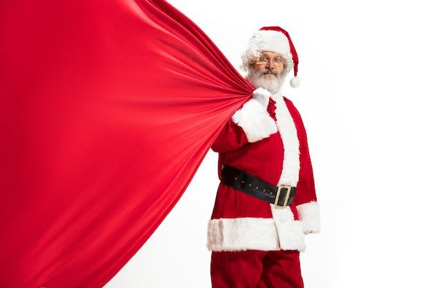 Babbo natale tirando un'enorme borsa piena di regali di natale isolati su sfondo bianco. modello maschio caucasico in costume tradizionale. capodanno 2020, regali, vacanze, atmosfera invernale. copyspace per il tuo annuncio.