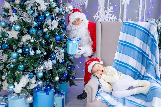 Babbo natale mette un regalo sotto l'albero mentre il bambino dorme, il concetto di capodanno e natale