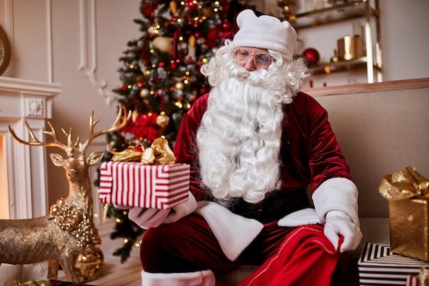 Babbo natale mette i regali nella sua grande borsa rossa per augurare ai bambini un buon natale.
