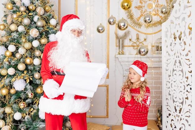 Babbo natale legge una lettera di un bambino all'albero di natale, capodanno e concetto di natale