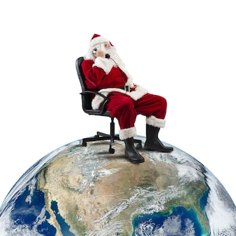 Babbo natale riceve richieste via telefono seduto su una sedia in un grande mondo