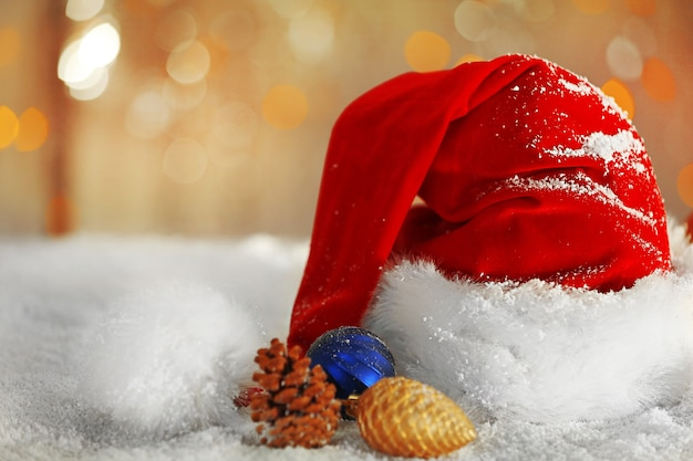Cappello di babbo natale rosso con decorazioni natalizie sulla neve artificiale su sfondo lucido, primi piani