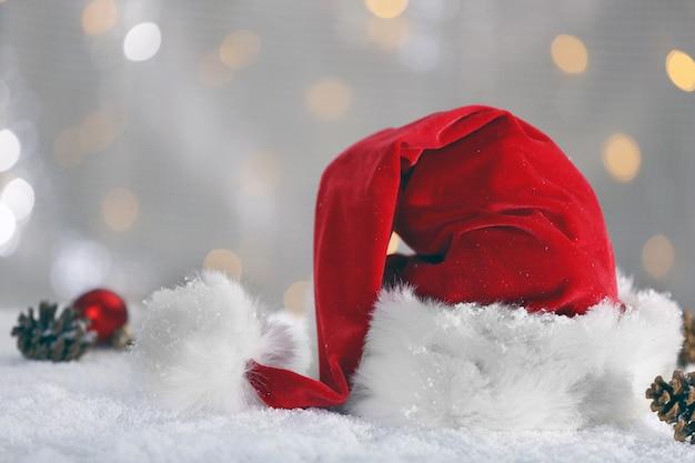 Cappello di babbo natale rosso con decorazioni natalizie sulla superficie lucida