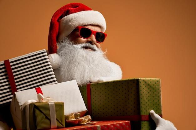 Babbo natale in occhiali da sole rossi con scatole regalo guardando lontano