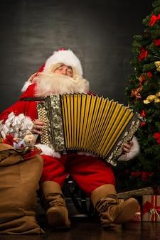 Babbo natale seduto in poltrona vicino all'albero di natale a casa e suonare musica sulla fisarmonica